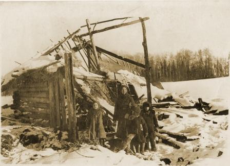 Свидетельница тарана, жительница д. Доронино Павлюченкова У.Г. с детьми, возле своего дома, разрушенного в октябрьские бои 1941 года. Февраль 1942 года.