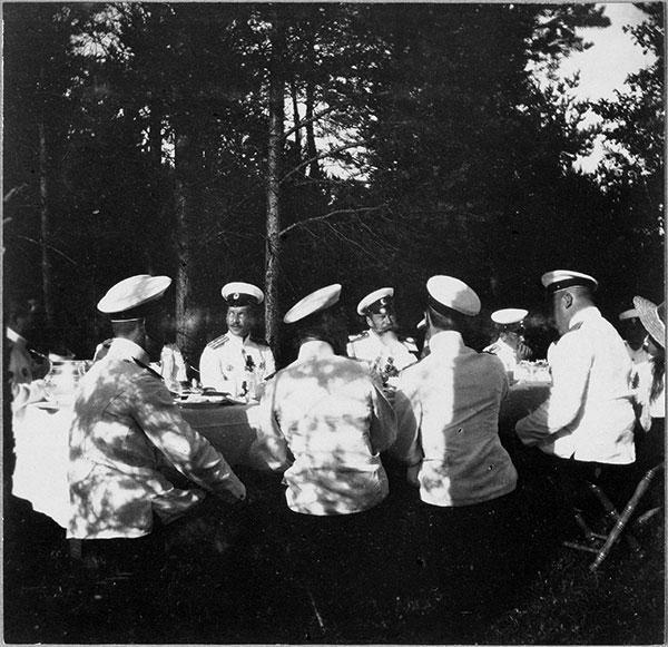 Николай II (справа, с траурной повязкой на кителе) за столом с офицерами-моряками. Финляндские шхеры, 1913 г.